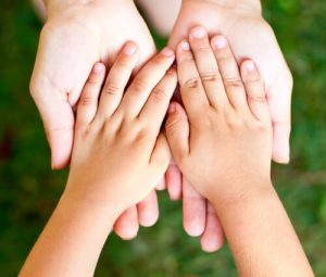 parent supporting child's hands